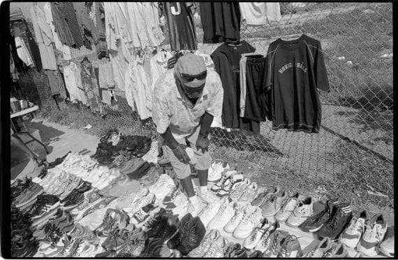 Photo of a man selling shirts and shoes on the street