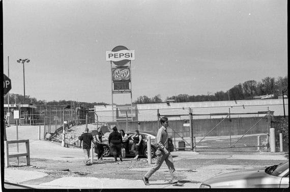Photo of youth hanging around Pepsi sign