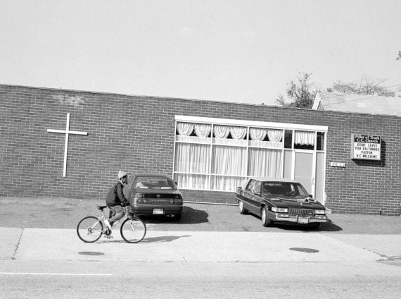 Photo of boy biking by church