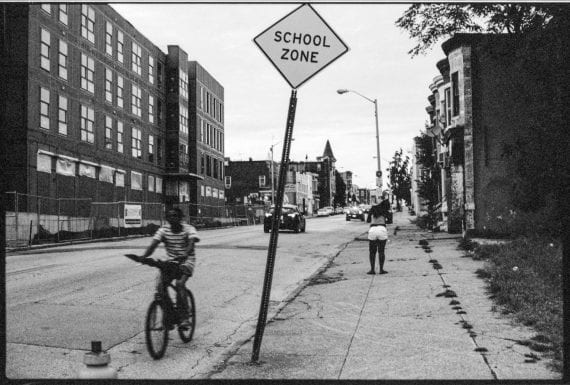 Photo of young person biking through a school zone